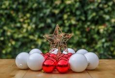 Muitas bolas brancas e vermelhas do Natal que cercam uma estrela em uma tabela de madeira Fotografia de Stock