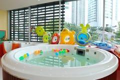 Muitas bolas infláveis coloridas na água e em muitas projetam os anéis de borracha para o jogo da criança fotos de stock