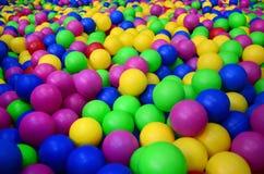 Muitas bolas plásticas coloridas em um kids& x27; ballpit em um campo de jogos Foto de Stock