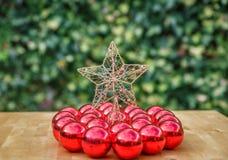 Muitas bolas vermelhas do Natal em torno de uma estrela, em uma tabela de madeira Fotografia de Stock