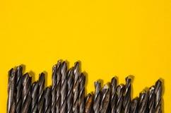Muitas brocas em um fundo amarelo brilhante Fotografia de Stock