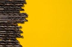 Muitas brocas em um fundo amarelo brilhante Foto de Stock