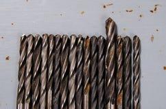 Muitas brocas em um fundo pintado do metal uma broca mais grande Imagem de Stock Royalty Free