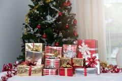 Muitas caixas de presente dos presentes de Natal em uma tabela com tre do Natal Imagens de Stock