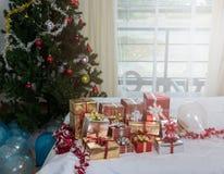 Muitas caixas de presente dos presentes de Natal em uma tabela com tre do Natal Fotografia de Stock Royalty Free