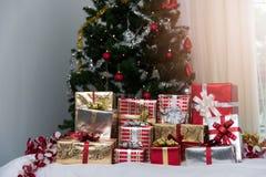 Muitas caixas de presente dos presentes de Natal em uma tabela com tre do Natal Imagens de Stock Royalty Free