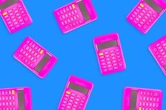 Muitas calculadoras plásticas cor-de-rosa digitais dispersadas na tabela azul no escritório fotografia de stock