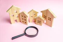 Muitas casas de madeira em um fundo cor-de-rosa e em uma lupa O conceito de encontrar uma casa nova para comprar ou a propriedade imagens de stock