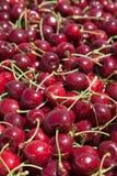 Muitas cerejas maduras vermelhas em um escaninho pronto para ser empacotado para a venda foto de stock