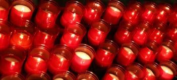 muitas chamas vermelhas das velas iluminaram-se pelo fiel no lugar de w Fotografia de Stock Royalty Free