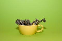 Muitas chaves velhas são dentro do copo amarelo Foto de Stock