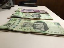 Muitas contas dos pesos mexicanos distribu?ram e propaga??o em uma mesa colorida bege fotografia de stock