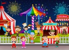 Muitas crianças e trabalhador dos povos que tem o divertimento no parque de diversões na noite Foto de Stock