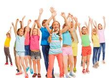 Muitas crianças felizes levantam junto as mãos acima no ar Fotos de Stock