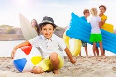 Muitas crianças na praia e no menino com bola inflável imagens de stock
