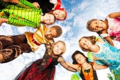 Muitas crianças, trajes de Dia das Bruxas olham para baixo no círculo Foto de Stock