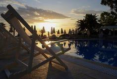 Muitas espreguiçadeiras brancas estão perto da piscina contra o contexto de um céu do alvorecer e de guarda-chuvas de praia fotografia de stock
