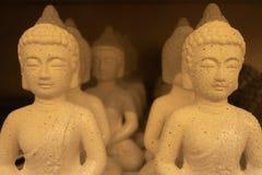 Muitas estatuetas idênticas da Buda estão na prateleira na loja imagem de stock