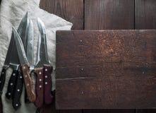 Muitas facas de cozinha diferentes velhas em uma tabela marrom Imagens de Stock Royalty Free