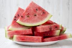 Muitas fatias de melancia suculenta madura em uma placa branca, close-up Imagem de Stock Royalty Free