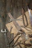 Muitas ferramentas oxidadas velhas dispersaram no tstolu de madeira Vista de acima imagem de stock