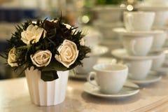 Muitas fileiras de copos de café branco puros na tabela branca fotos de stock
