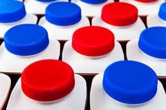 Muitas garrafas com tampas plásticas vermelhas e azuis com os produtos láteos ácidos igualmente girados da leiteria próximos acima Fotos de Stock