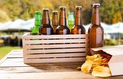 Muitas garrafas da cerveja e do bloco das microplaquetas na tabela de madeira no fundo borrado do verão imagem de stock