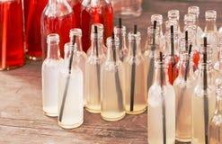 Muitas garrafas pequenas com uma vitamina de refrescamento bebem em uma tabela de madeira em um café exterior Fotografia de Stock