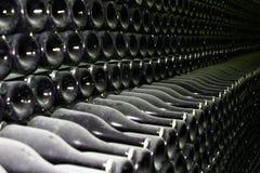 Muitas garrafas velhas do champanhe, empilhadas no fim da adega de vinho acima fotografia de stock