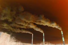 Muitas grandes tubulações de que vão o fumo, as emanações de exaustão e os pastores sujos, acima da cidade, foto de stock royalty free