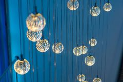 Muitas lâmpadas de incandescência redondas que penduram em um fundo azul fotografia de stock royalty free
