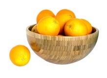 Muitas laranjas maduras na bacia de madeira grande isolada no branco Fotos de Stock Royalty Free