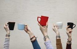 Muitas mãos diferentes que guardam copos de café foto de stock