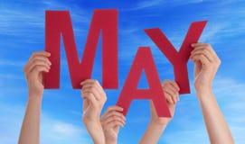 Muitas mãos dos povos que guardam a palavra vermelha podem céu azul Imagens de Stock Royalty Free