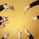 Muitas mãos que apontam adiante ou para fora no fundo alaranjado Imagem de Stock