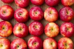 Muitas maçãs vermelhas com folhas em um fundo de madeira. Imagens de Stock