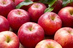 Muitas maçãs vermelhas com folhas em um fundo de madeira Fotos de Stock