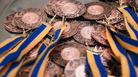 Muitas medalhas de bronze com as fitas azuis amarelas em uma bandeja de prata Fotos de Stock Royalty Free