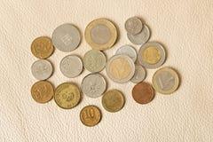 Muitas moedas dispersadas em um fundo de couro imagens de stock royalty free