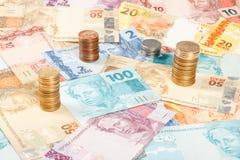 Muitas notas e moedas reais novas Fotos de Stock Royalty Free