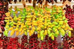 Muitas pimentas amarelas e vermelhas que penduram no mercado imagens de stock