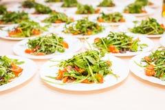 Muitas placas com salada fresca com rúcula da carne, dos tomates, a nuts e a misturada dos verdes, mesclun, mache na tabela Saudá Foto de Stock