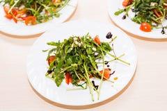 Muitas placas com salada fresca com rúcula da galinha, dos tomates, a nuts e a misturada dos verdes, mesclun, mache na tabela Sau Fotos de Stock Royalty Free