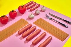 Muitas salsichas cruas com massa e vegetais no fundo cor-de-rosa e amarelo, vista superior Fotos de Stock