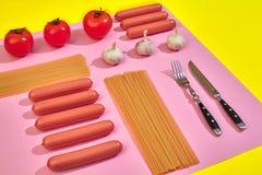 Muitas salsichas cruas com massa e vegetais no fundo cor-de-rosa e amarelo, vista superior Foto de Stock Royalty Free