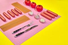 Muitas salsichas cruas com massa e vegetais no fundo cor-de-rosa e amarelo, vista superior Foto de Stock