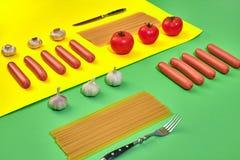 Muitas salsichas cruas com massa e vegetais no fundo verde e amarelo, vista superior Fotografia de Stock