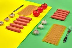 Muitas salsichas cruas com massa e vegetais no fundo verde e amarelo, vista superior Imagens de Stock