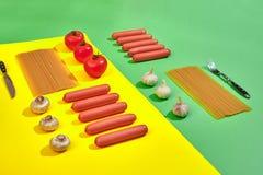 Muitas salsichas cruas com massa e vegetais no fundo verde e amarelo, vista superior Imagens de Stock Royalty Free